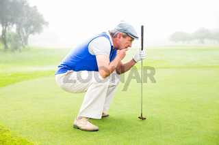 Serious golfer kneeling on the putting green