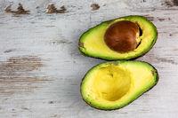 Cut avocado fruit on wooden background