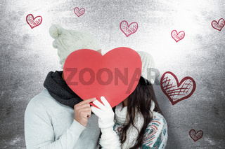 Composite image of smiling couple holding paper heart