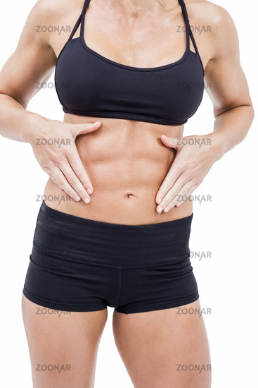 Female athlete touching her abs