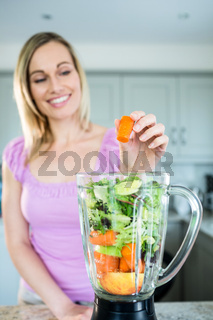 Blonde woman preparing a smoothie in the kitchen