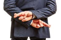 Geschäftsmann kreuzt Finger hinter Rücken