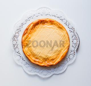 Käsekuchen auf weißem Hintergrund mit Tortenspitze