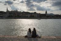 Women sitting at river Danube, Budapest, Hungary