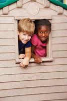 Zwei Kinder schauen durch Fenster im Spielhaus