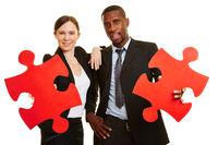 Geschäftsleute halten rote Puzzleteile
