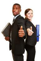 Geschäftsleute mit Akten halten Daumen hoch