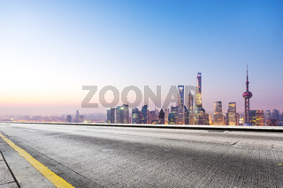 empty road and cityscape in blue sky