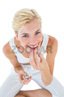 Smiling blonde woman holding pill and looking at camera