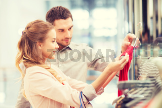 happy young couple choosing dress in mall