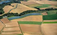 Solar field between autumnal farmland