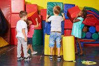 Kinder beim Aufräumen im Kindergarten
