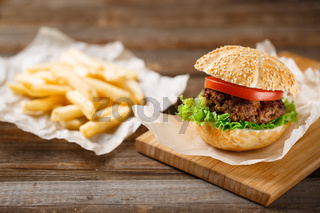 Homemade hamburgers and french fries on wooden table