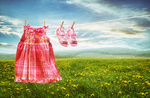 Dress and sandals on clothesline in fields of dandelions