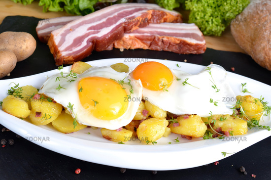 Two fried eggs with fried potatoes