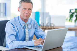 Thoughtful businessman using laptop computer
