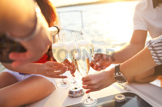 Happy friends with glasses of champagne on yacht. Vacation, travel, sea and friendship concept