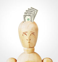 Many dollar banknotes are inserted into a human head as into a money box. Abstract image with a wooden puppet