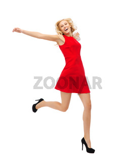 happy young woman in red dress jumping high