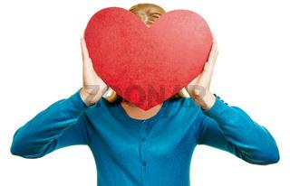Anonyme Frau hält rotes Herz vor Gesicht