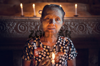 Burmese woman prayingwith candlelight
