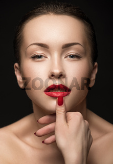 Beautiful Woman with red lips touching her Lips.