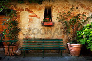 Retro bench outside old Italian house in a small town of Pienza, Italy. Vintage