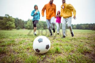 Friends running towards football