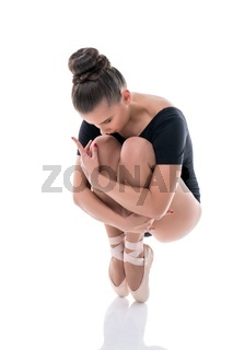 Ballerina on pointes, clutching her knees to chest