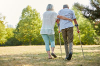 Frau hilft Mann beim laufen mit Krücken