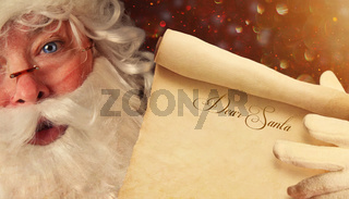 Closeup of Santa holding a Dear Santa scroll