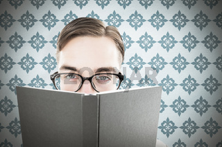 Composite image of geeky man looking over book