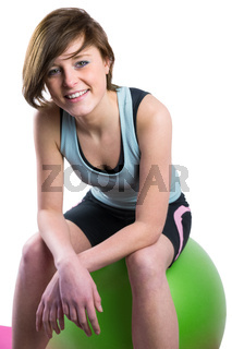 Pretty brunette looking at camera and smiling on fitness ball