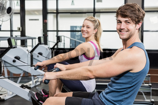 Portrait of a man and woman working out on rowing machine