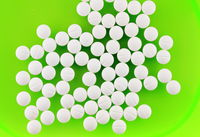 Pile of white pills on green plate