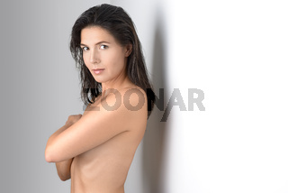 Schöne Frau bedeckt Ihre Brust und schaut in die Kamera