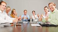 Geschäftsleute halten Daumen hoch im Business Meeting
