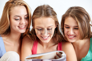 friends or teen girls reading magazine at home