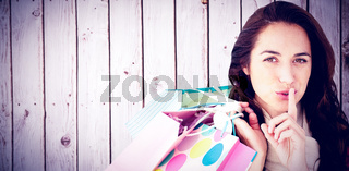 Composite image of woman wearing a scarf and holding shopping bags