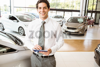 Smiling salesman using tablet near a car