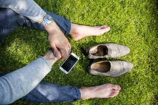 Barefoot man sitting on grass