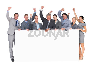 Excited business team holding poster
