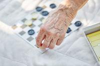 Senioren spielen das Brettspiel Mühle
