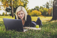 student girl with laptop studying in park
