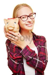 Teenager mit Brille und Sparschwein