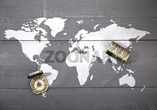 World map with compass and treasure on dark black wooden background