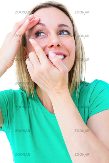 Smiling blonde applying contact lens