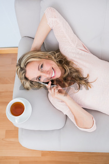 Smiling blonde on the phone with cup of tea on couch