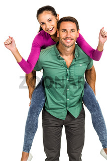 Cheerful man giving piggy back to his girlfriend