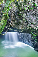 Small waterfall under a huge rock with moss a